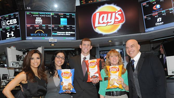 """IMAGE DISTRIBUTED FOR FRITO-LAY - The three finalists in the Lay's """"Do Us A Flavor"""" contest, Christina Abu-Judom, second left, Tyler Raineri, center, and Karen Weber-Mendham, second right, are joined by actress Eva Longoria, left, and chef Michael Symon at the New York Stock Exchange, Tuesday, Feb. 12, 2013, in New York. The finalist flavors - Lay's Cheesy Garlic Bread, Lay's Chicken & Waffles and Lay's Sriracha flavored potato chips - are now available on store shelves nationwide.  (Photo by Diane Bondareff/Invision for Frito-Lay/AP Images)"""