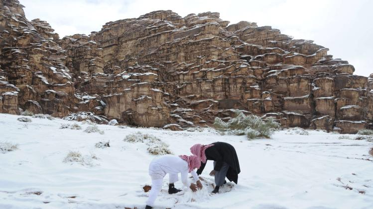 Saudi men make a snowman after a snowstorm in Alkan village, west of Saudi Arabia