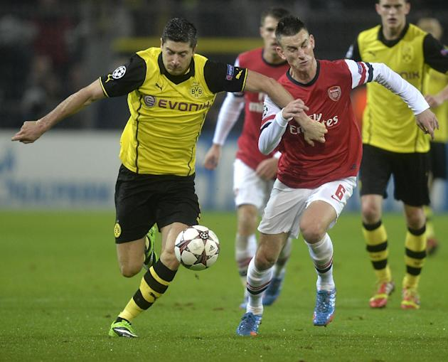 Dortmund's Robert Lewandowski, left, and Arsenal's Laurent Koscielny challenge for the ball during the Champions League group F soccer match between Borussia Dortmund and Arsenal FC in Dortmund, Germa
