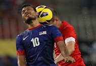 Malaysia&#39;s Safee Sali (L) fights for the ball with Singapore&#39;s Mustafic Fahrudin during their AFF Suzuki Cup Group B football match in Kuala Lumpur on November 25, 2012. Singapore beat the defending Southeast Asian champions 3-0