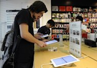Customers try out the iPad 2 at an Apple authorised retail shop in Singapore