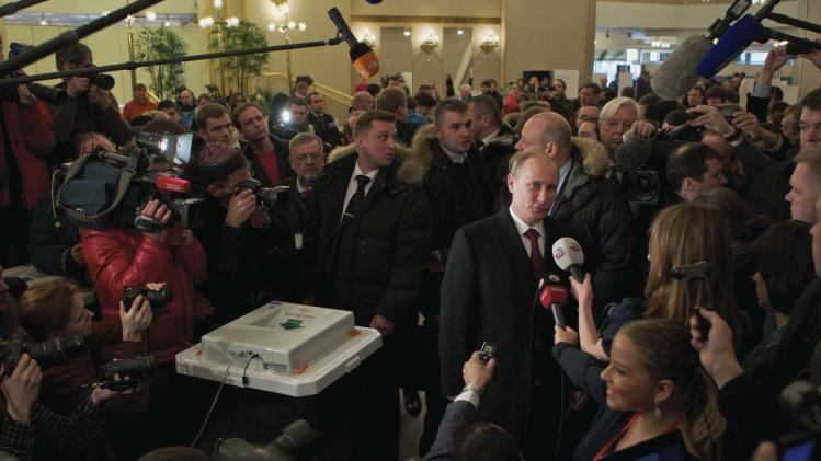 Russian Prime Minister and presidential candidate Vladimir Putin, center right, talks to the media at a polling station  in Moscow, Russia, Sunday, March 4, 2012. Polling stations have opened across Russia's vast expanse for the presidential election widely expected to return Vladimir Putin to the Kremlin. (AP Photo/Ivan Sekretarev)