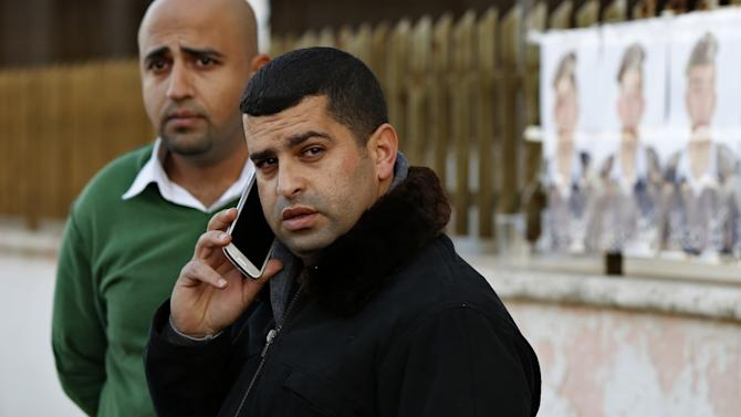 Safi, the brother of Islamic State captive Jordanian pilot Kasaesbeh, speaks on the phone as he waits for news at his clan's headquarters in Amman