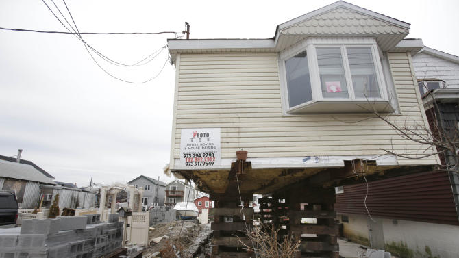 FILE- In this April 11, 2013, file photo, a home in the process of being raised is seen in the Broad Channel section of Queens, New York. A year and a half after Superstorm Sandy decimated New York City's coastline, a city-run program that was supposed to rebuild wrecked homes has only begun construction on three houses, and officials say they will need another $1 billion from the federal government in order to help every homeowner in need. Homeowners who lost everything in the storm are furious with the lack of progress made by the Build-It-Back program, which was created by former Mayor Michael Bloomberg to primarily help New Yorkers repair, rebuild and elevate homes, though some funding was also designated to aid renters and owners of multi-family properties. (AP Photo/Seth Wenig, File)