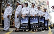 Demonstrators dressed as workers take part in a protest against Taiwanese technology giant Foxconn, which manufactures Apple products in mainland China, outside an Apple retail outlet in Hong Kong. Apple admitted some of its suppliers continued to overwork and underpay employees, as it threw open its factory doors to monitors after a spate of suicides at the Foxconn plant