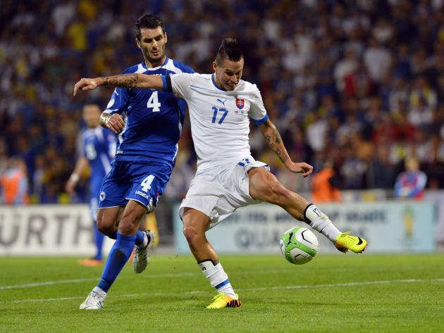 Slovakia's Marek Hamsik fights for the ball with Bosnia's Emir Spahic during their 2014 World Cup qualifying soccer match in Zilina