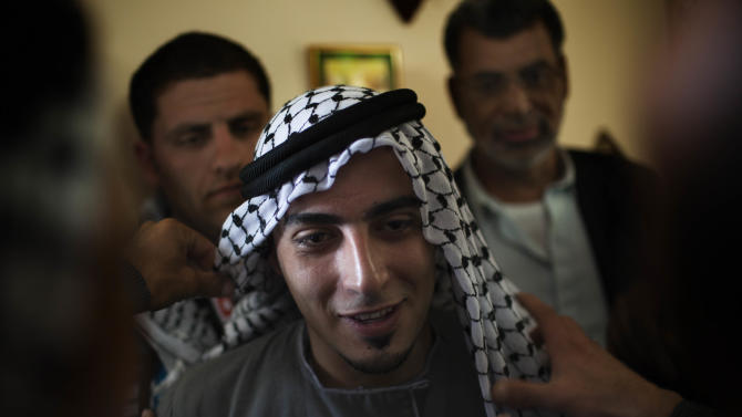 In this photograph made on Thursday, April 12, 2012, groom Thaer Qasem is dressed by Palestinians during his wedding with Maha Surougi in the West Bank village of Deir Istiya, near Nablus. The bride and the groom, Syrian citizens with Palestinian roots were invited by the Palestinian government to get married in the West Bank. (AP Photo/Bernat Armangue)