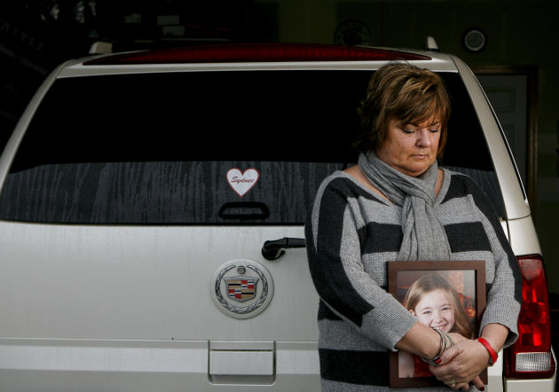 <p>               In this Saturday, Dec. 22, 2012 photo, Judy Neiman holds a photo of her daugher, Sydnee, in front of her 2006 Cadillac Escalade at her home in West Richland, Wash. Sydnee died in late 2011 after Neiman accidentally backed over her with the SUV. Although there is a law in place that calls for new manufacturing requirements to improve the visibility behind passenger vehicles, the standards have yet to be mandated because of delays by the U.S. Department of Transportation. (AP Photo/Kai-Huei Yau)