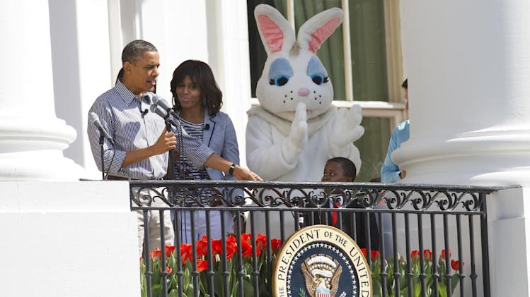 President Barack Obama, accompanied by first lady Michelle Obama, and the Easter Bunny, points toward Robby Novak, 9, of Henderson, Tenn., known as Kid President as he speaks from the Truman Balcony at the start of the annual White House Easter Egg Roll on the South Lawn of the White House in Washington, Monday April 1, 2013. (AP Photo/Jacquelyn Martin)