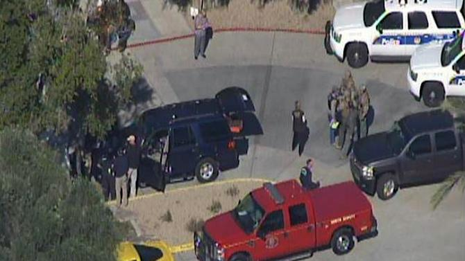 This frame grab provided by abc15.com shows the scene at a Phoenix office complex where police say someone shot at least three people on Wednesday, Jan. 30, 2013. Officer James Holmes said the victims were taken to hospitals and did not know if their injuries were life threatening. (AP Photo/abc15.com) MANDATORY CREDIT