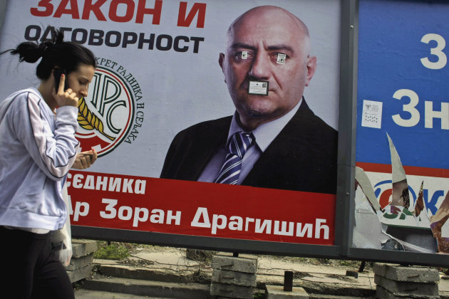 A woman passes by a defaced election poster of Zoran Dragisic, a presidential candidate, in Belgrade, Serbia, Saturday, May 5, 2012. The first round vote on Sunday for president, and votes for a 250 seat national assembly and local councils pit pro EU democrats against nationalists who have gained in popularity with the EU&#39;s own economic troubles, which have dimmed the bloc&#39;s allure for many Serbs. (AP Photo/ Marko Drobnjakovic)