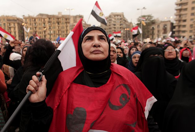 An Egyptian woman holds a national flag as she listens to speakers, not pictured, in Tahrir Square in Cairo, Egypt, Tuesday, Dec. 4, 2012. Hundreds of black-clad riot police deployed around the Itihad