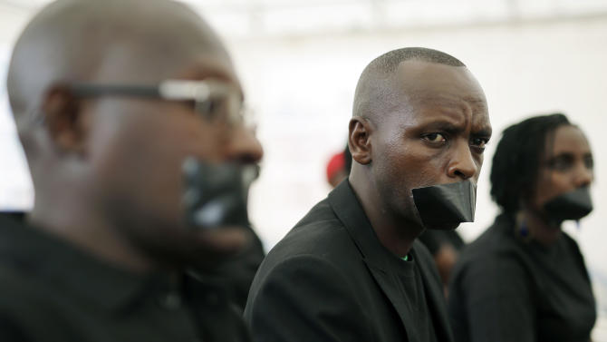 Journalists with tape on their mouths gather on the occasion of World Press Freedom Day, Bujumbura, Burundi, Sunday, May 3, 2015. In the wake of demonstrations protesting against the move by President Pierre Nkurunziza to seek a third term, the government shut down access to some social networks and closed a private radio station. (AP Photo/Jerome Delay)