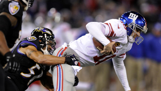 New York Giants quarterback Eli Manning, right, is sacked by Baltimore Ravens inside linebacker Brendon Ayanbadejo in the first half of an NFL football game in Baltimore, Sunday, Dec. 23, 2012. (AP Photo/Nick Wass)