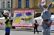 Football fans pose next to a banner calling for the release of Ukraine&#39;s jailed ex-premier Yulia Tymoshenko in front of the Euro 2012 fan zone in Kiev