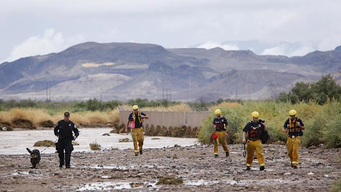 Members of the Henderson police and fire departments head back to their vehicles after conducting a search of the Duck Creek Channel for 17-year-old Green Valley High School student William Mootz in Henderson, Nev.  on Aug. 22, 2012.  Crews resumed the search Thursday for Mootz, who somehow fell into a drainage wash in Henderson, Nev., which had filled quickly after a morning downpour a day earlier.  (AP Photo/Las Vegas Review-Journal, Jason Bean)