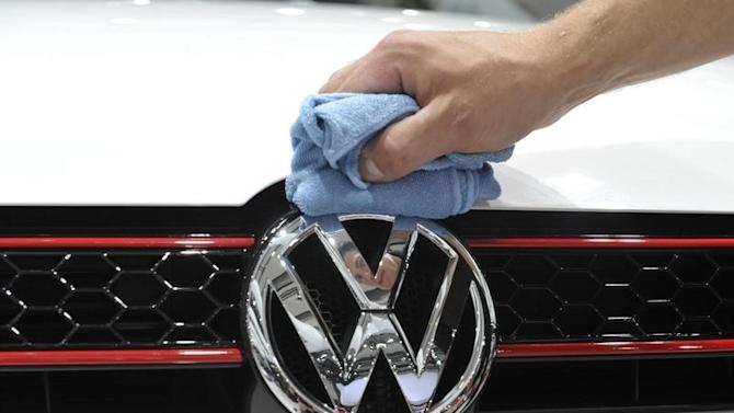 A man polishes the Volkswagen logo on a vehicle of an exhibition which is part of the annual shareholders meeting of Volkswagen AG in Hamburg