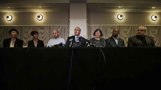 Attorney David Frederick, center, speaks during a news conference, Tuesday, April 9, 2013, in Philadelphia, after a hearing to determine whether the NFL faces years of litigation over concussion-related brain injuries. Listening, from left Eleanor Perfetto, the widow of former NFL player Ralph Wenzel; Lisa McHale, the widow of former NFL player Tom McHale; former NFL player Kevin Turner, Frederick, Mary Ann Easterling, the widow of former NFL player Ray Easterling, and former NFL players Dorsey Levens, and Bill Bergey. (AP Photo/Matt Rourke)