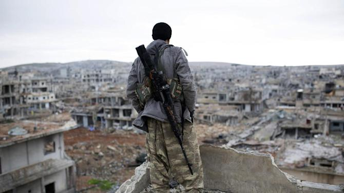 FILE - In this Jan. 30, 2015, file photo, a Syrian Kurdish sniper looks at the rubble in the Syrian city of Ain al-Arab, also known as Kobani. Turkey's dramatic air campaign against the Islamic State and Kurdish forces has created a bit of a conundrum for President Barack Obama, who is leading the fight against one of Turkey's targets while relying heavily on the other target.  (AP Photo, File)