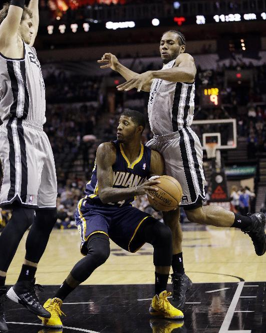 Indiana Pacers' Paul George, center, is pressured by San Antonio Spurs' Tiago Splitter, left, of Brazil, and Kawhi Leonard, right, during the first half of an NBA basketball game, Saturday, De