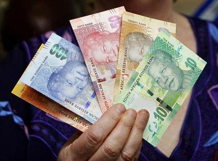 The hand of South African Reserve Bank Governor Gill Marcus is seen holding South Africa's new rand banknotes in Pretoria