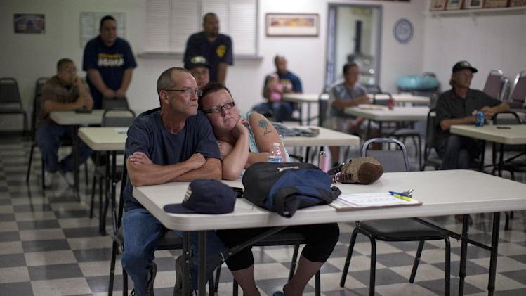 Dawn, right, and Randy Cornell, watch the presidential debate at the United Steelworkers Local 4856 Union Hall with fellow union members, Wednesday, Oct. 3, 2012, in Henderson, Nev. President Barack Obama and Republican presidential candidate Mitt Romney faced off, Wednesday night, in their first debate. (AP Photo/Julie Jacobson)