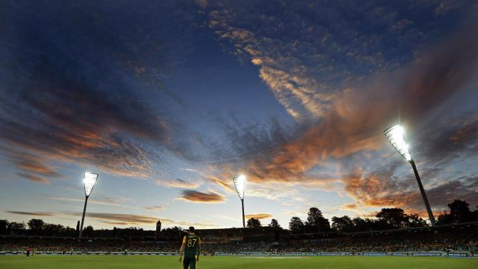 South Africa's Abbott stands near the boundary at sunset during the Cricket World Cup match against Ireland at Manuka Oval in Canberra