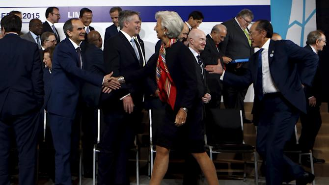 Turkish Central Bank Governor Basci and IMF Managing Director Lagarde shake hands next to other global policymakers after a family picture of the G-20 group at the 2015 IMF/World Bank Annual Meetings in Lima, Peru