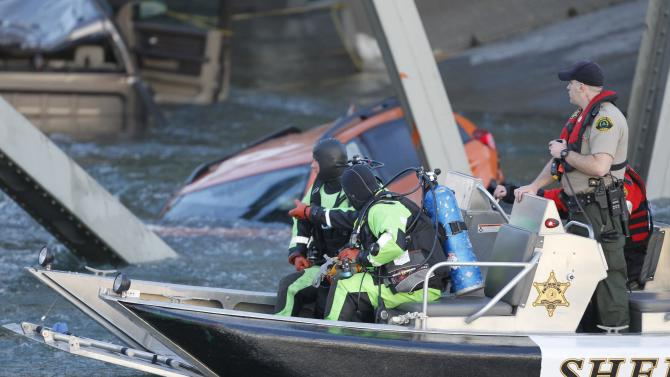A rescue boat and divers search near a portion of the Interstate-5 bridge that is submerged after it collapsed into the Skagit river dumping vehicles and people into the water in Mount Vernon, Wash., Thursday, May 23, 2013 according to the Washington State Patrol. (AP Photo/Joe Nicholson)
