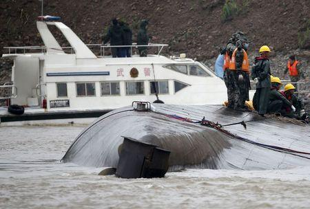 Rescue workers and a capsized ship are seen during a media trip to the site of the sinking, organized by the Chinese goverment, in the Jianli section of Yangtze River