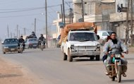 "Syrian residents drive motorcycles and cars to flee during fighting between rebels and regime forces in the village of Kurnaz, close to the western city of Hama, on January 27, 2013. The Syrian opposition appealed Monday for hundreds of millions of dollars (euros) to step up the revolt against Bashar al-Assad, as the president asserted his forces had made ""significant gains"" in the conflict"