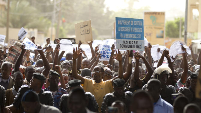 People march along a central street as thousands rallied in a show of support for the recent military coup, in Bamako, Mali Wednesday, March 28, 2012.  The body representing nations in western Africa has suspended Mali and has put a peacekeeping force on standby in the most direct threat yet to the junta that seized control of this nation in a coup last week. Blue and white sign at right says: 'Movement in support of the reestablishment of democracy and the restoration of the state'. White signs with blue lettering read: 'Responsibility assumed. Thank you CNRDR' - CNRDR is the junta. (AP Photo/Rebecca Blackwell)