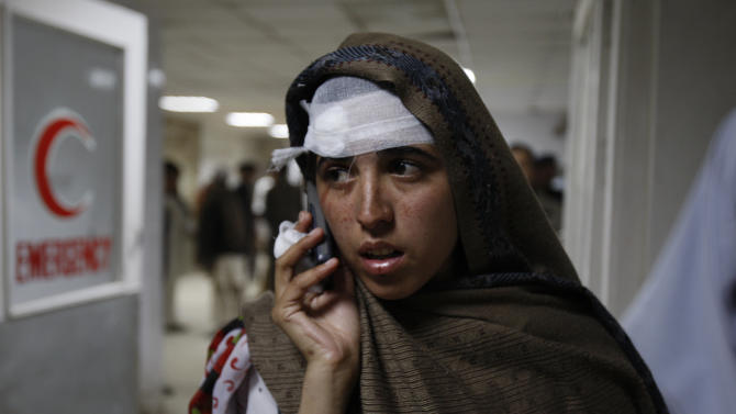 A Pakistani girl, who injured  in a rocket attack by militants, talks on her cell phone after receiving initial treatment at a local hospital in Peshawar, Pakistan on Saturday, Dec. 15, 2012. Militants fired three rockets at an airport in the northwestern Pakistani city of Peshawar on Saturday night, killing several people and wounding dozens, officials said. (AP Photo/Mohammad Sajjad)
