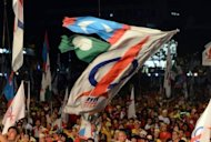 Supporters wave various opposition coalition party flags at a huge opposition rally in Penang, Malaysia on May 3, 2013. Anwar said only fraud can stop his Malaysian opposition from scoring a historic election win as the rival sides launched a last-ditch campaign blitz Saturday on the eve of a tense vote