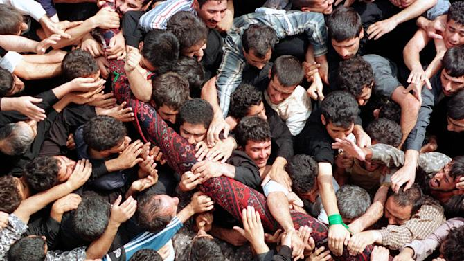 "FILE-- In this Sept. 29, 2000, file photo, Iranian mourners try to touch and carry the sacred rug after it has been ""washed"" in Ardahal near city of Kashan about 260 kms south of capital of Tehran, Iran. It has been more than 1300 years since the people of the Iranian hamlet of Fin and thousands from areas in the vicinity of the city of Kashan, in the historic central province of Isfahan, first began commemorating the anniversary of the martyrdom of Sultan-Ali son of Imam Mohammad Baqer who is the fifth Imam in the Prophet Mohammad's holy house hold.The commemoration is held annually by on the fourth Friday of September near his mausoleum on the skirts of the Karkas mountain range and a nearby river. The ceremonies are named Rug Washing in the local jargon because the body of the martyred Shiite saint was wrapped up in one before it was buried. The rug woven by the people of Kashan -- well-known for their rug weaving skill-- had been originally given to Sultan-Ali when he was alive to use as a praying rug. The rug used in these ceremonies is a replica of the original. (AP Photo/Hasan Sarbakhshian, File)"