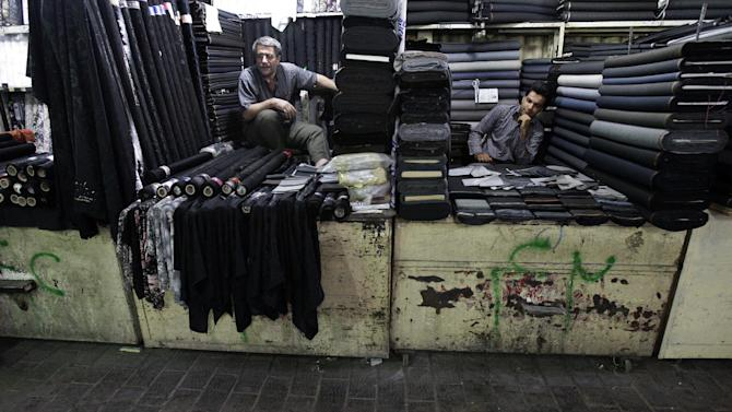 In this picture taken on Saturday, July 14, 2012, two Iranian textile merchants wait for customer in Tehran's old main bazaar, Iran. While Iran's mainstay oil exports remains the centerpiece of Western sanctions _ intended to wring concessions on Iran's nuclear program and ease Israeli threats of a military strike _ the Islamic Republic hangs on as OPEC's third-largest exporter as it feeds the hungry energy markets in China, India and across Asia. But less noted _ but potentially more unsettling to Iran's leaders in the coming months _ is the increasing pinch on the workaday economy: The commerce, transactions and trading that provide the paychecks and economic lifelines for millions of people. (AP Photo/Vahid Salemi)