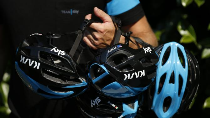 A Team Sky member prepares riders helmets in front of their hotel before a team training session in Zeist, Netherlands