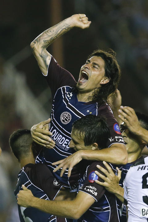 Argentina's Lanus' Ismael Blanco, top, celebrates after scoring against Brazil's Ponte Preta during the Copa Sudamericana final soccer match in Buenos Aires, Argentina,  Wednesday, Dec. 11