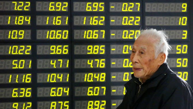 An investor walks in front of the stock price monitor at a private securities company Tuesday, Nov. 27, 2012 in Shanghai, China. Asian stock markets rose Tuesday after talks over Greece's financial crisis ended with an agreement on how to reduce its debt load, paving the way for the cash-strapped country to receive the next installment of a bailout loan. (AP Photo)