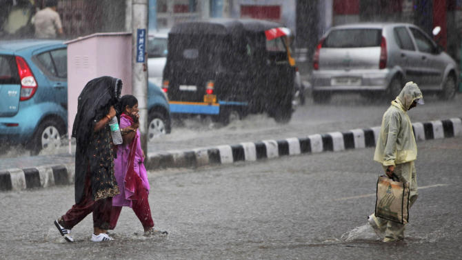 People wade through a flooded street as it rains in Jammu, India, Friday, July 8, 2011. India's monsoon rains are crucial for farmers whose crops feed hundreds of millions of people. (AP Photo/Channi Anand)