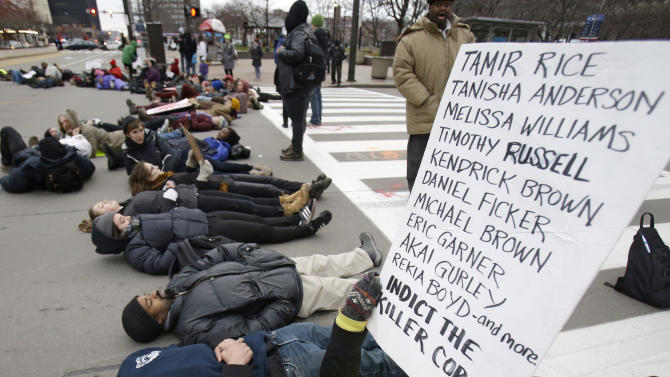 Demonstrators lay down in Public Square Tuesday, Nov. 25, 2014, in Cleveland, during a protest over the weekend police shooting of Tamir Rice. The 12-year-old was fatally shot by a Cleveland police officer Saturday after he reportedly pulled a replica gun at the city park. (AP Photo/Tony Dejak)