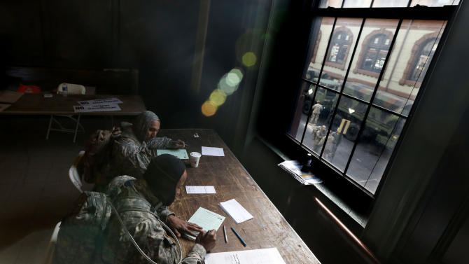 With members of the New Jersey National Guard seen through a window as they congregate outside of Hoboken City Hall, specialists Abdul Scott, bottom right, of Elizabeth, N.J., and Cullin King, of Hillside, N.J., fill out and affidavits as they cast their vote on Election Day, Tuesday, Nov. 6, 2012, in Hoboken, N.J. The servicemen, are performing duties in the city which was hit by severe flooding caused by Superstorm Sandy. (AP Photo/Julio Cortez)