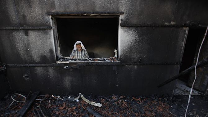 A Palestinian man inspects a house after it was torched in a suspected attack by Jewish settlers killing an 18-month-old  Palestinian child, his four-year-old brother and parents were wounded, according to a Palestinian official from the Nablus area. at Duma village near the West Bank city of Nablus, Friday, July 31, 2015. (AP Photo/Majdi Mohammed)