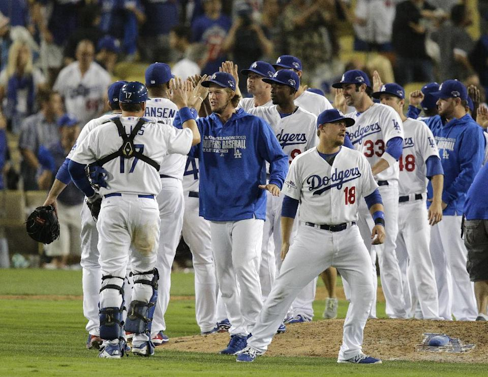 Los Angeles Dodgers players celebrate after they beat the Atlanta Braves 13-6 in Game 3 of the National League division baseball series, Sunday, Oct. 6, 2013, in Los Angeles. (AP Photo/Jae C. Hong)