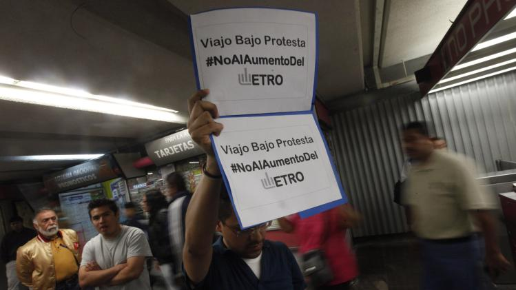 A man holds up a poster to protest against a fare hike, at Pino Suarez subway station in Mexico City