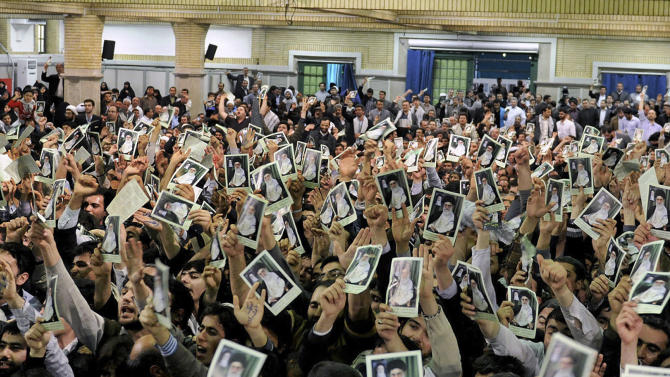 In this photo released by the official website of the Iranian supreme leader's office, Iranian well wishers attending the speech of Supreme Leader Ayatollah Ali Khamenei hold up his picture at a mosque inside the leader's housing compound in Tehran, Iran, Saturday, Feb. 16, 2013.  Khamenei said Saturday that his country is not seeking nuclear weapons, but that no world power could stop Tehran's access to an atomic bomb if it intended to build one. (AP Photo/Office of the Supreme Leader)