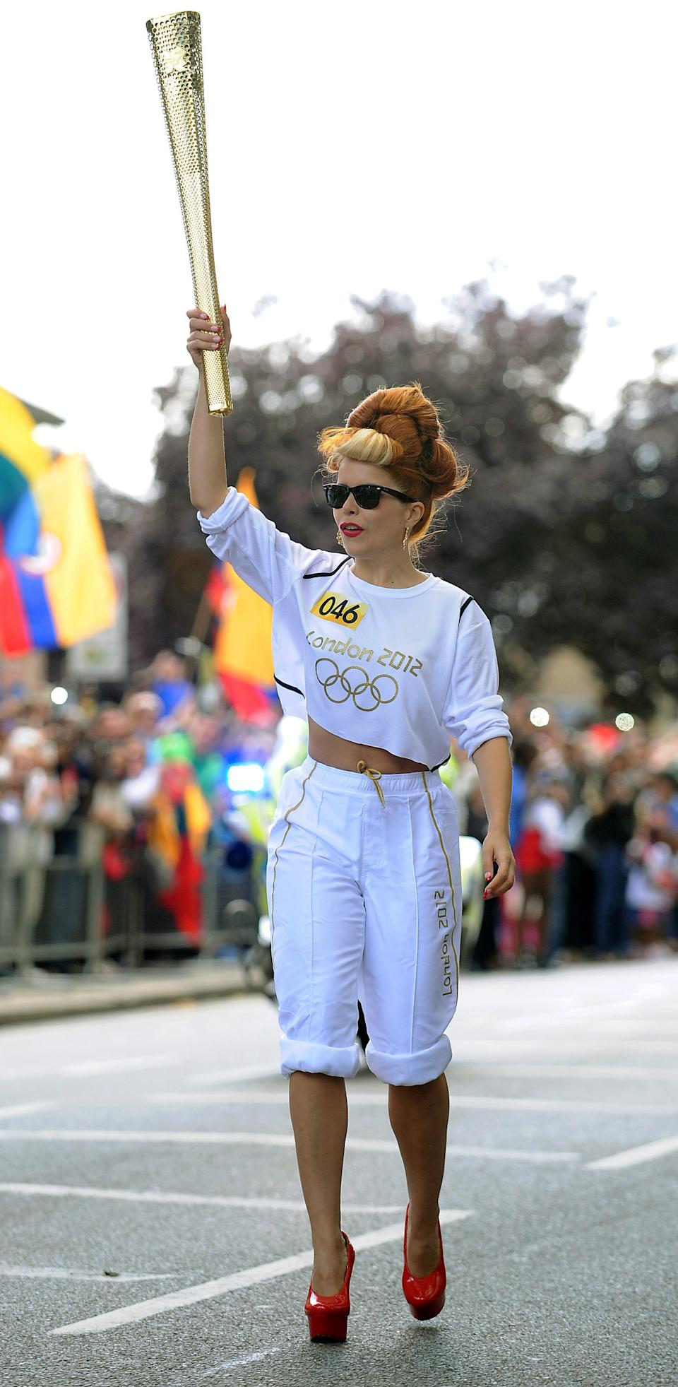 In this Saturday, July 21, 2012,  photo provided by LOCOG, singer Paloma Faith carries the Olympic Flame on the Torch Relay leg through London. The opening ceremonies of the Olympic Games are scheduled for Friday, July 27. (AP Photo/LOCOG, Joe Giddens)