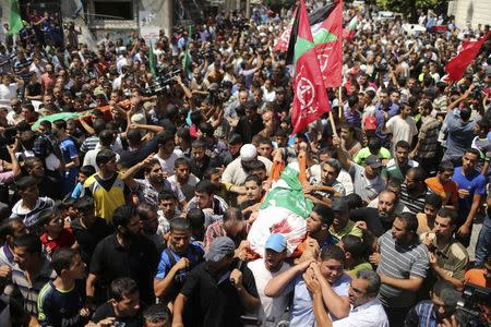Palestinians march during the funeral of the wife of Deif, his infant son Ali and other Palestinians in the Gaza Strip