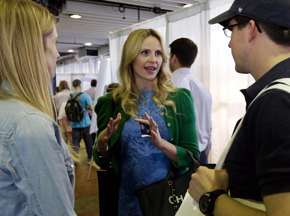"This May 18, 2013 photo shows pregnancy advise guru Rosie Pope, center, speaking with attendees at the New York Baby Show in New York. Pope is the author of the pregnancy guide, ""Mommy IQ,"" and also has her own maternity clothing line. (AP Photo/Richard Drew, file)"