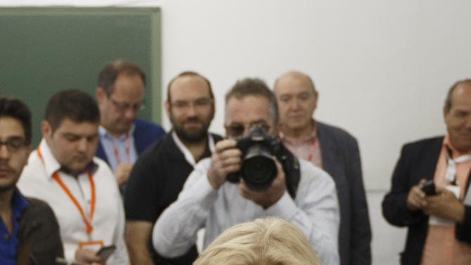 Local candidate for 'Ahora Madrid' (Madrid Now) party Manuela Carmena shows her identification before casting her vote at a polling station in Madrid, Spain, Sunday, May 24, 2015. Local elections in much of Spain could see two upstart parties end nearly four decades of dominance by the conservative Popular Party and the center-left Socialists. (AP Photo/Daniel Ochoa de Olza)
